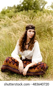 Young girl in ethnic clothes walking in fields. Fashion photo, folklore style