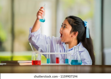 young girl examining a test tube in a science class.