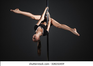 Young girl exercise pole dance before a gray background