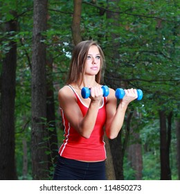 Young girl exercising with dumbbells in the park