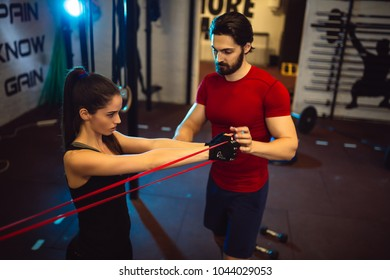Young girl exercising at the gym with a male personal trainer.