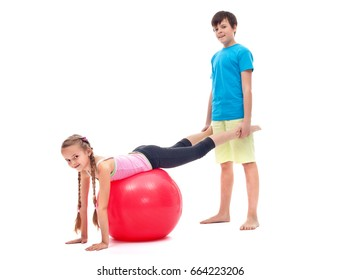 Young girl exercising with a large gymnastic rubber ball - helped by a boy, isolated