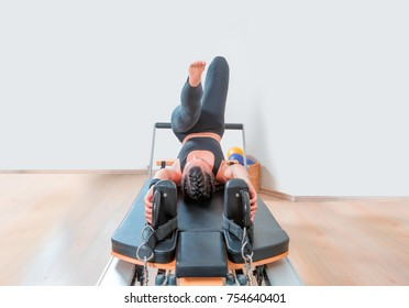 Young girl exercising on pilates reformers beds