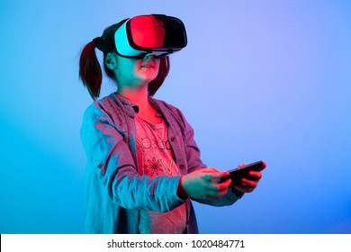 Young girl experiencing VR headset game on colorful background. Child using a gaming gadget for virtual reality. Futuristic goggles at young age. Virtual technology