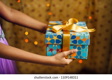 A young girl extending a hand with a decorative gift box. Partial view of an arm holding gift pack.