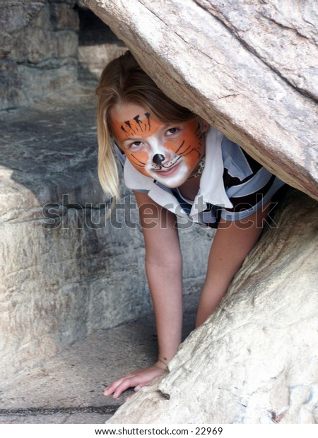 young girl with face painted like a tiger