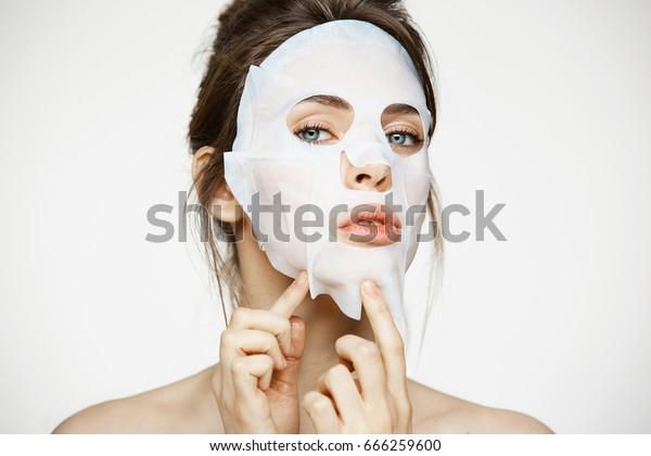 白い背景にカメラを見る、顔面を持つ若い女の子。コスメティック手順。美容院と美容院。