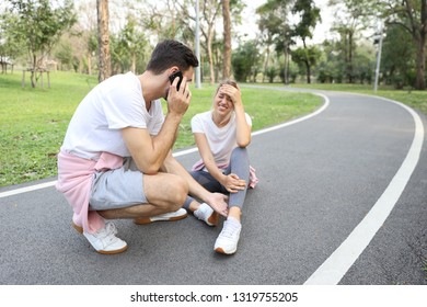 young girl fall down because of the dizziness from too much exercise and young man is helping by using cell phone calling someone