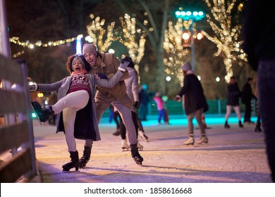 A young girl falling down at ice rink on a beautiful magical night with her boyfriend. Skating, closeness, love, together