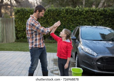 Young girl and father giving high five to each other near the car