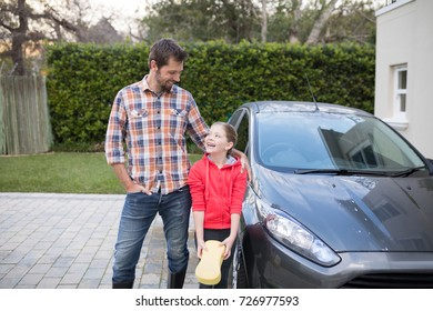 Young girl and father standing near the car