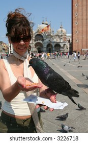 Young girl is feeding the birds in Venice
