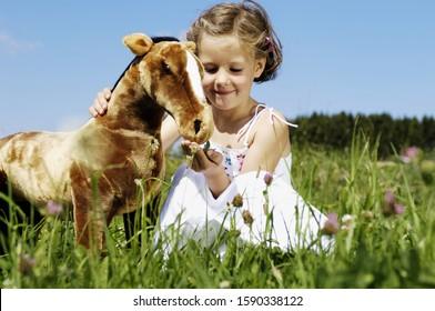 Young girl feeding stuffed animal horse in meadow