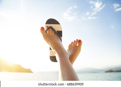 Young girl feet in colorful flip-flop sandal on sea beach