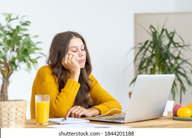 Young girl fell asleep in front of laptop. Cute woman is bored, tired or overworked. Cozy home environment. Pretty female in bright yellow jumper working on laptop at home