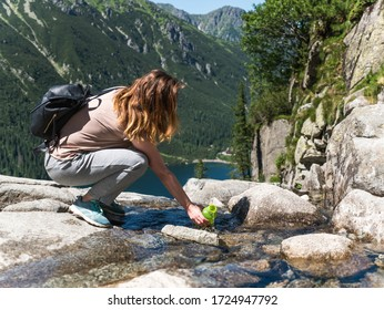 A young girl fills a bottle of water from a stream of a cold mountain lake in the Tatras, Lake Czarny Staw. - Shutterstock ID 1724947792