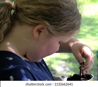 Young girl with fishing rod and worms beside a lake in a park