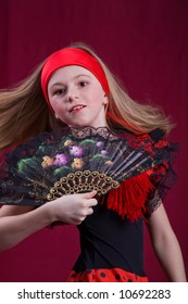 a young girl in flamenco dress posing in front of red background