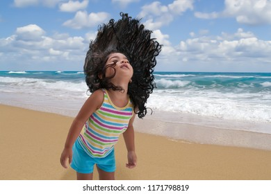 Young girl flings her long black hair upwards with excitement at the beach while the waves crash to the shore in the background.
