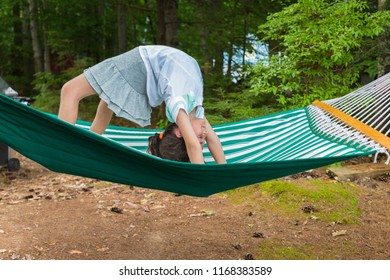 A young girl is flipping outside down in a green hammock