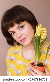 Young girl florist with yellow hyacinth flower. Large portrait.