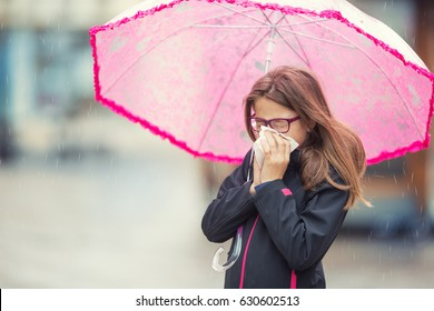 Young girl with flu blowing her nose with a tissue paper under umbrella Pre-teen girl sneezing and wearing warm clothes against cold weather.