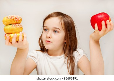 A young girl with food contemplates whether she would prefer healthy apples or unhealthy donuts.