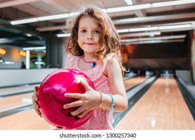 Young girl with freckles holding a pink bowling ball, happy with her color choise.