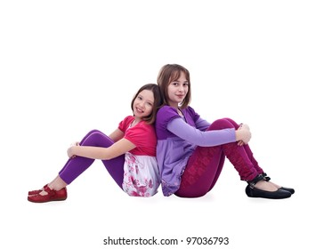 Young girl friends sitting back to back - isolated