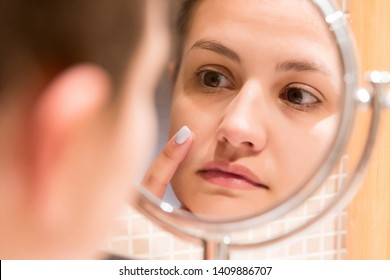 Young girl in front of a bathroom mirror putting cream on a red pimple. Beauty skincare and wellness morning concept.
