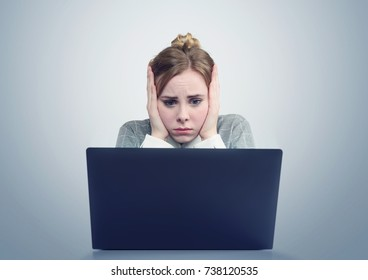 Young girl in front of a laptop clutched her head.