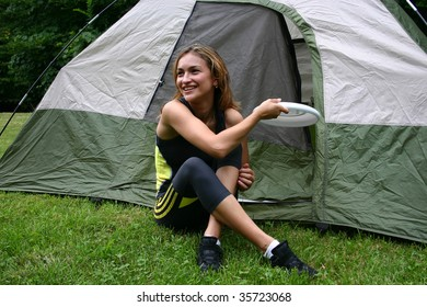 young girl in front of tent playing with a Frisbee