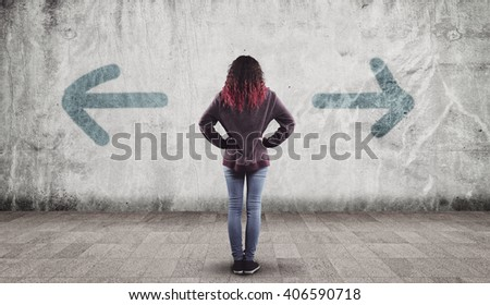 Young girl in front of a wall painted with arrows towards opposite directions.  'left or right'