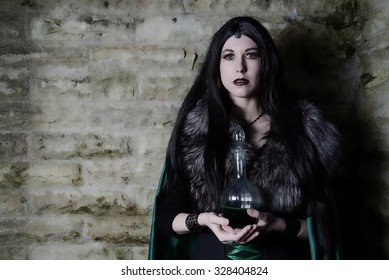Young girl with fur cape and flask with potion. Looking like Halloween suit.