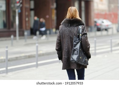 Young girl with fur coat and shoulder bag, walking on street in the winter