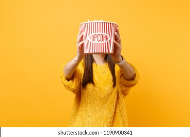 Young girl in fur sweater watching movie film and covering face with bucket of popcorn isolated on bright yellow background. People sincere emotions in cinema, lifestyle concept. Advertising area