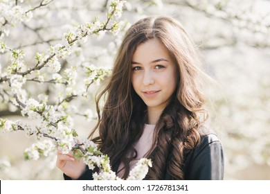 Young girl in the garden under a flowering tree.
