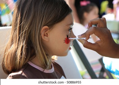 young girl gets a ladybug painted on her face