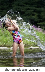 A young girl getting a big splash of water on a hot summer day