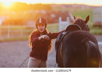 Young girl getting her horse ready for riding in the padlock. Jockette. Horseriding.