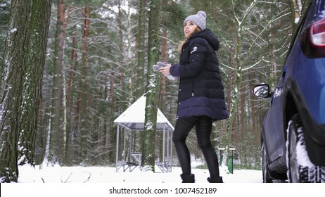 Young girl getting out of the car in a snowy forest