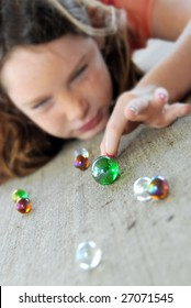 young girl getting ready to flick shooter during marbles