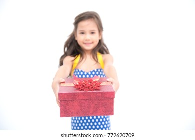 Young girl give suprise gift. Young cute white girl giving a gift present box, looking cute. Isolated in white. Birthday and family concept.