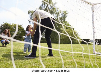 Young girl gives football to dad in goal, while mum watches