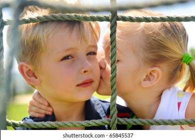 Young girl gives her brother a kiss on the cheek