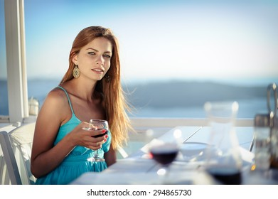 Young girl with glass of wine at Santorini island, Greece