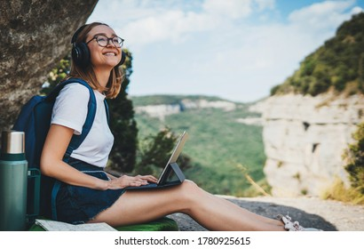 young girl with glasses and backpack enjoying summer vacation in mount listen music in headphones and laptop in nature, fun traveler woman planning hiking walk looks at online map on tablet device