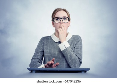 Young girl in glasses behind the keyboard in front of the computer in fear. Virus attack concept