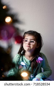 A young girl with glasses is decorating a Christmas tree and is happily playing with the decorations.