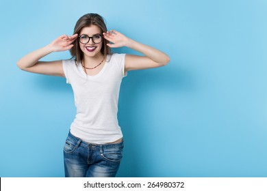 Young girl with glasses in a modern style on a background of a blue wall